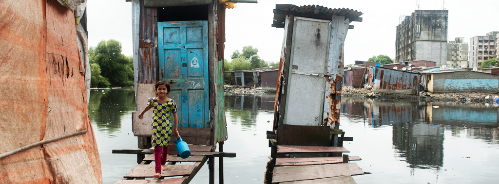 Eriam Sheikh,7 year old comes out after using the toilet on stilts or floating toilet built over a drain passing by Rafiq Nagar in Mumbai. PHOTO:UN Water